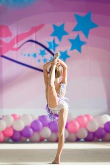 Kleine schöne turnerin auf teppich. der entzückende turner nimmt an wettbewerben im rhythmischen turnen teil