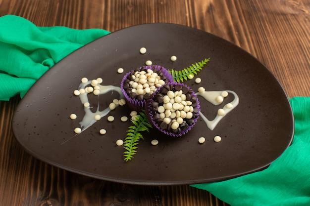 Kleine schokoladenbrownies mit schokoladenstückchen in dunkler platte auf holz