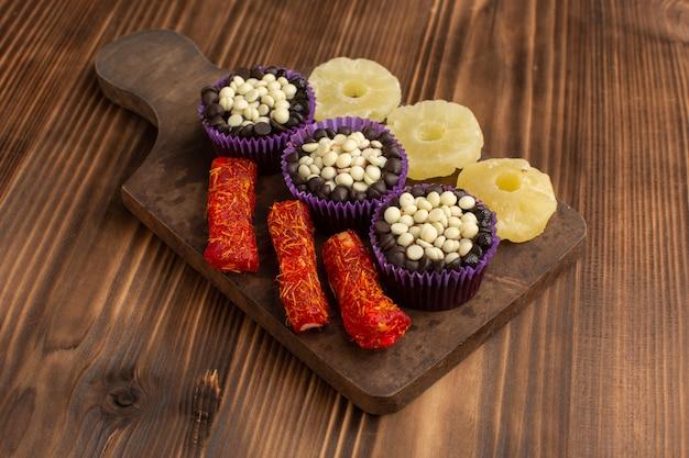 Kleine schokoladenbrownies mit schokoladenstückchen zusammen mit ananasringen und nougat auf holz