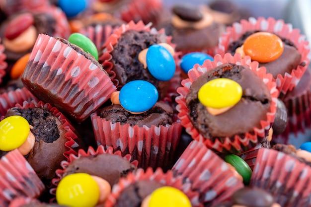 Kleine schokoladencupcakes zusammen mit süßigkeiten ist ein straßenessen auf dem lokalen markt in thailand, nahaufnahme. thailändisches süßes essen