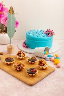 Kleine schokoladenkuchen der vorderansicht mit bonbons und blauer geburtstagstorte auf dem rosa schreibtisch
