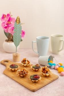 Kleine schokoladenkuchen der vorderansicht mit bonbons und heißem tee auf der zuckersüßen farbe des rosa schreibtischkuchens