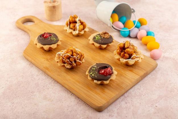 Kleine schokoladenkuchen der vorderansicht mit nüssen und süßigkeiten auf der süßen zuckerfarbe des hölzernen schreibtisches