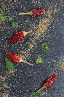 Kleine schoten aus rotem pfeffer, petersilienblättern und gemahlenem koriander. schwarzer hintergrund. flach legen