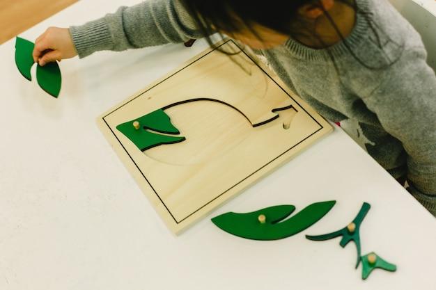 Kleine schüler in einem kindergarten, der pädagogische puzzlespiele handhabt.