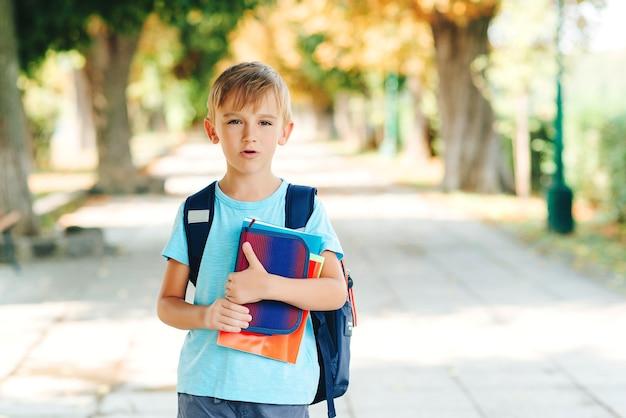 Kleine schüler mit negativen emotionen gehen zur schule. bildung, zurück zum schulkonzept. unglücklicher schuljunge mit büchern in händen und rucksack auf der straße.