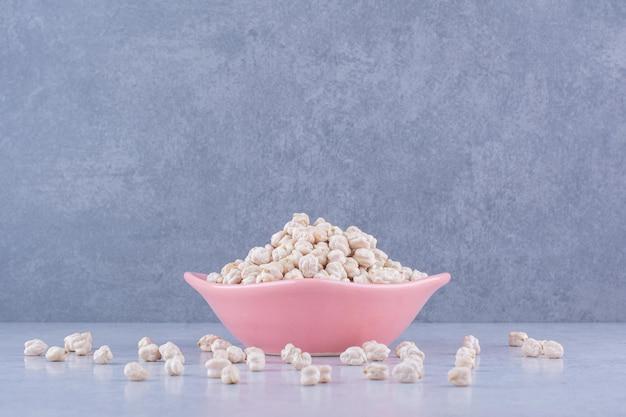 Kleine schüssel, die übermäßig mit einem haufen kichererbsen gefüllt ist, auf marmoroberfläche