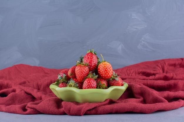 Kleine schüssel erdbeeren verschachtelt auf einem zerknitterten stapel tischdecke auf marmorhintergrund.