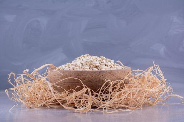 Kleine schüssel gefüllt mit hafer auf einem dekorativen strohhaufen auf marmorhintergrund. foto in hoher qualität