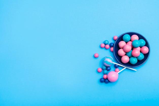 Kleine schüssel mit bonbons mit lutschern daneben