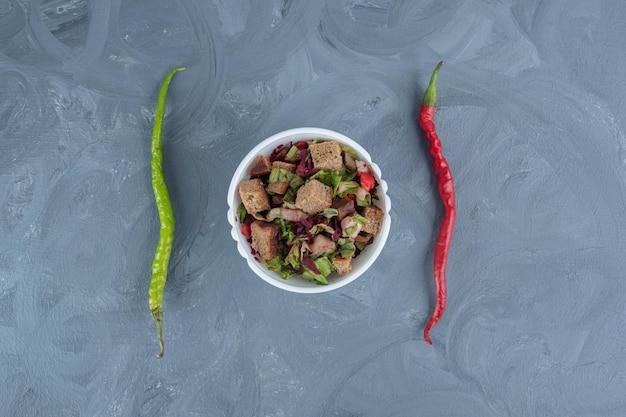 Kleine schüssel mit gemischtem salat in der mitte von zwei paprika auf marmortisch.