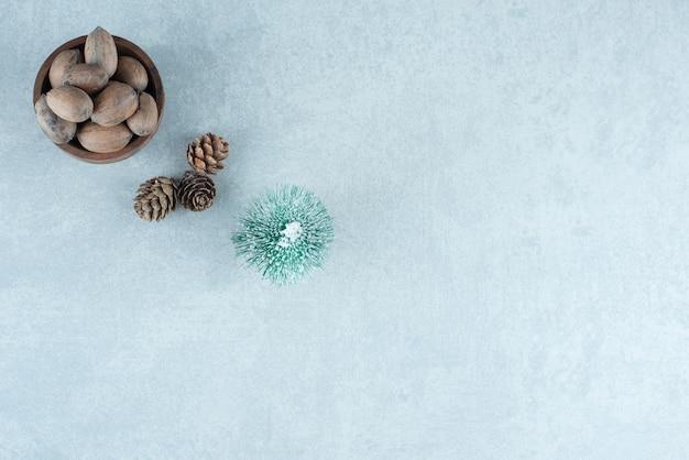Kleine schüssel mit mandeln, tannenzapfen und einer baumfigur auf marmor.