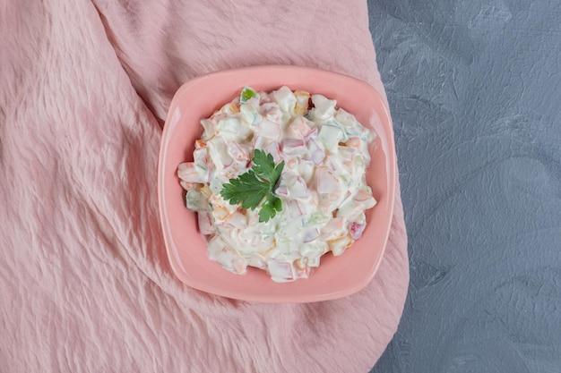 Kleine schüssel oliviersalat, garniert mit petersilienblättern auf rosa tischdecke auf marmorhintergrund. `