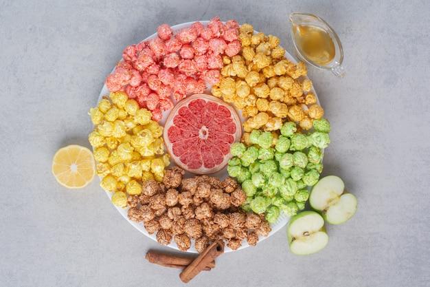 Kleine schüssel popcornbonbons und kartoffelchips auf marmor.