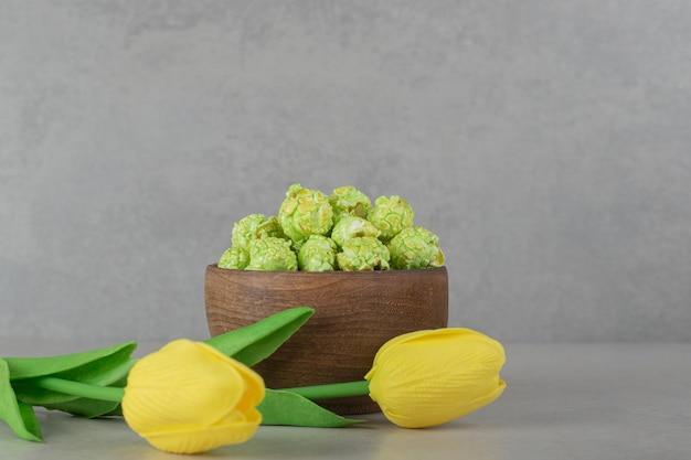 Kleine schüssel popcornbonbons und zwei tulpen auf marmorhintergrund.