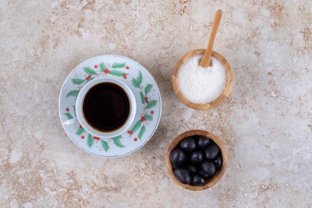 Kleine schüsseln zucker und süßigkeiten neben einer tasse kaffee