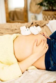Kleine schuhe für das ungeborene baby auf dem bauch der schwangeren. sie hält sanft ihre hände auf ihren bauch