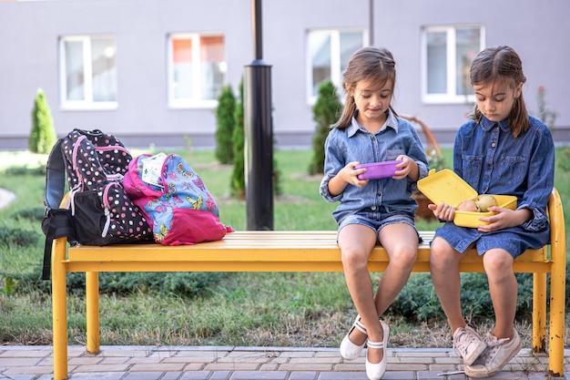 Kleine schulmädchen sitzen auf der bank im schulhof und essen aus brotdosen.