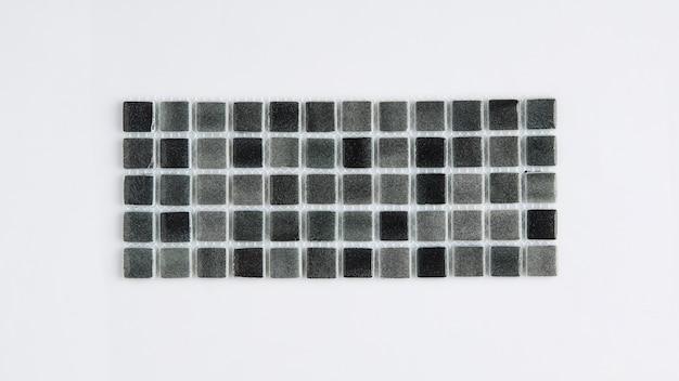 Kleine schwarze keramikfliese auf weißem hintergrund, draufsicht, majolika. für den katalog
