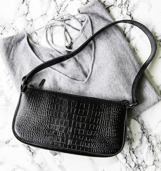 Kleine schwarze ledertasche und grauer damenpullover
