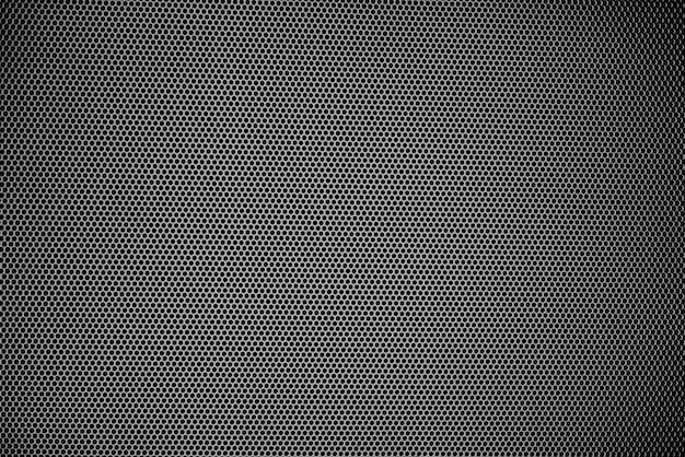 Kleine schwarze punkte, die das betrachten, werden von vielen schwarzen punkten des metallplattenhintergrundes geblendet