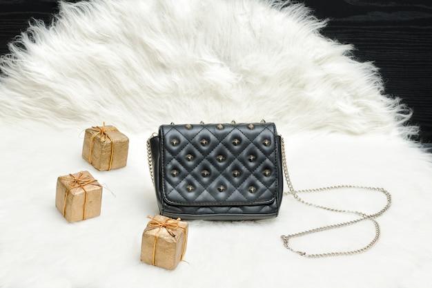 Kleine schwarze tasche und geschenkbox auf weißem fell. modisches konzept. urlaubseinkauf