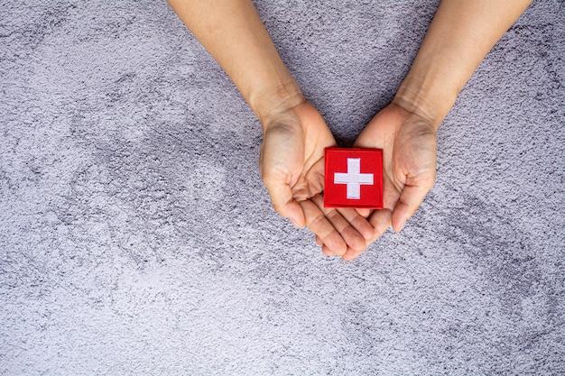 Kleine schweizer flagge in der hand. liebe, fürsorge, schutz und sicheres konzept.