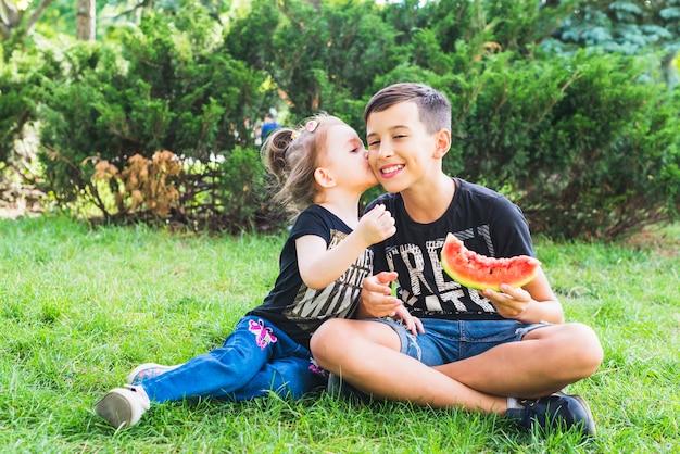 Kleine schwester, die ihren bruder hält wassermelonenscheibe küsst