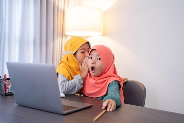 Kleine schwester flüstert ihren geschwistern etwas zu und ist schockiert, während sie zu hause einen laptop benutzt