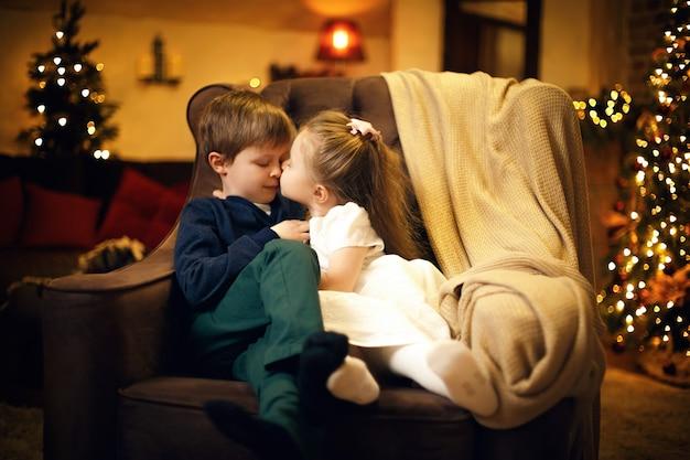 Kleine schwester küsst seinen bruder in einem festlichen silvester-interieur mit weihnachtsbaum und girlanden