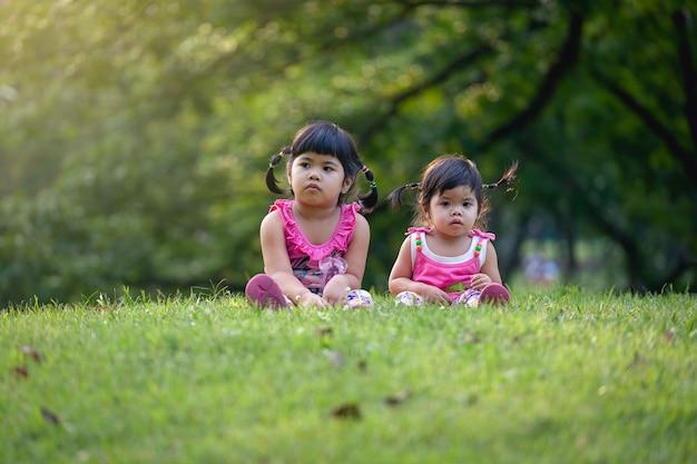 Kleine schwester spielen und sitzen auf dem grünen rasen im park. nette mädchen entspannen sich im park.