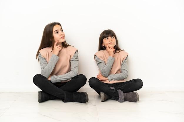 Kleine schwestern, die auf dem boden sitzen, isoliert auf weißem hintergrund, denken eine idee, während sie nach oben schauen
