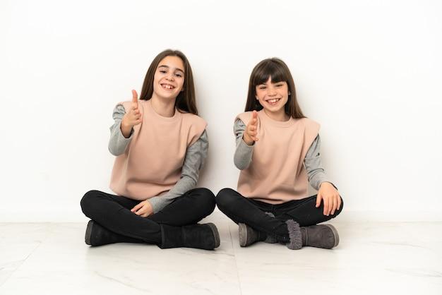 Kleine schwestern, die auf dem boden sitzen, schütteln sich die hände, um ein gutes geschäft abzuschließen