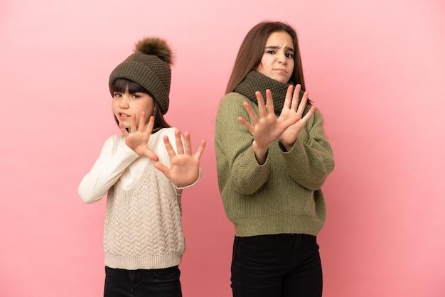 Kleine schwestern, die eine winterkleidung einzeln auf rosafarbenem hintergrund tragen, sind ein bisschen nervös und haben angst, die hände nach vorne zu strecken