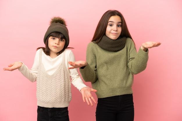 Kleine schwestern, die eine winterkleidung einzeln auf rosafarbenem hintergrund tragen und zweifel haben, während sie hände und schultern heben