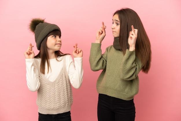 Kleine schwestern, die eine winterkleidung tragen, isoliert mit gekreuzten fingern und das beste wünschen