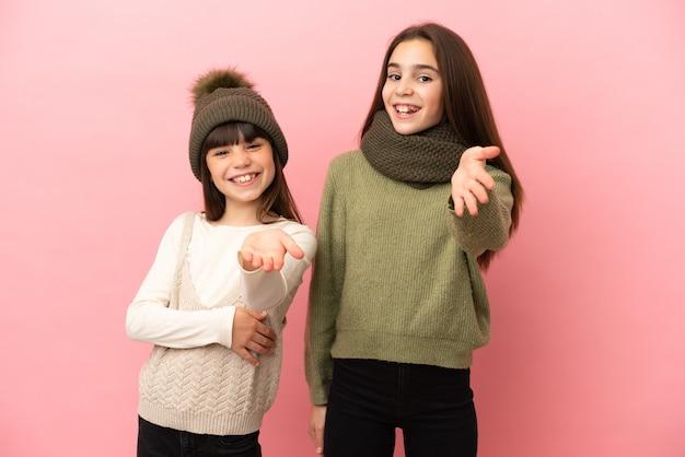 Kleine schwestern, die eine winterkleidung tragen, lokalisiert auf rosa hintergrund, händeschütteln für das schließen eines guten geschäfts