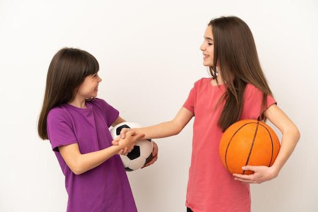 Kleine schwestern, die fußball und basketball spielen, isoliert auf weißem hintergrund, händeschütteln nach einem guten geschäft?