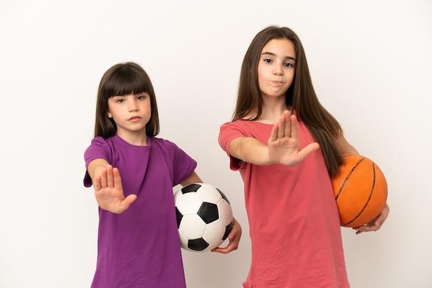 Kleine schwestern, die fußball und basketball spielen, isoliert auf weißem hintergrund, machen eine stopp-geste und leugnen eine situation, die falsch denkt