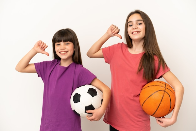 Kleine schwestern, die fußball und basketball spielen, isoliert auf weißem hintergrund, stolz und selbstzufrieden in liebe selbst konzept