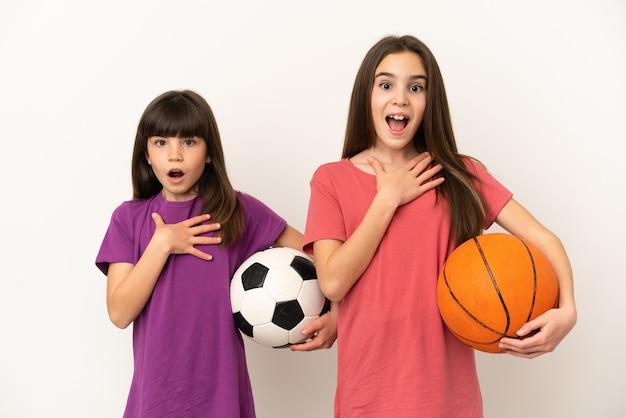 Kleine schwestern, die fußball und basketball spielen, isoliert auf weißem hintergrund, überrascht und schockiert, während sie nach rechts schauen