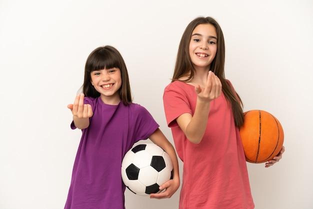 Kleine schwestern, die fußball und basketball spielen, lokalisiert auf weißem hintergrund, der einlädt, mit der hand zu kommen. schön, dass du gekommen bist