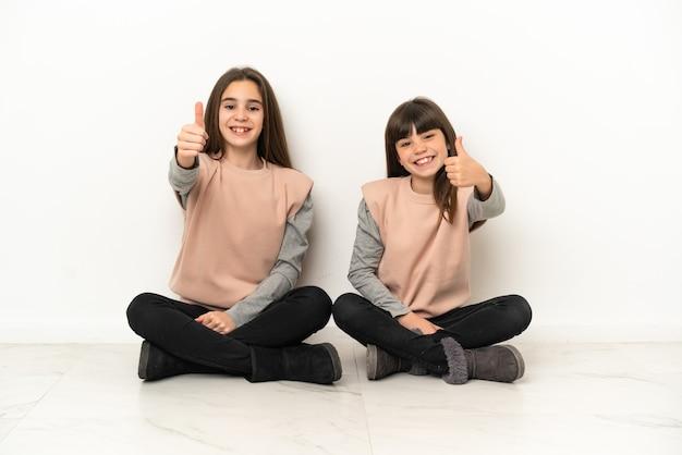 Kleine schwestern, die isoliert auf dem boden sitzen und eine geste mit dem daumen nach oben geben, weil etwas gutes passiert ist