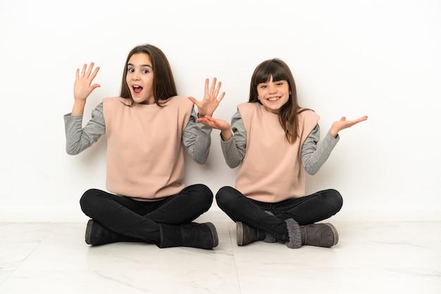 Kleine schwestern, die mit überraschung und schockiertem gesichtsausdruck isoliert auf dem boden sitzen