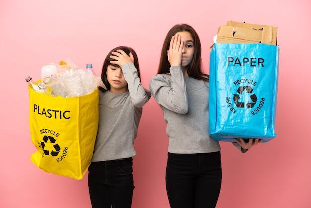 Kleine schwestern, die papier und plastik auf rosafarbenem hintergrund mit überraschung und schockiertem gesichtsausdruck recyceln