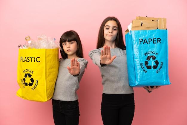 Kleine schwestern, die papier und plastik einzeln auf rosafarbenem hintergrund recyceln