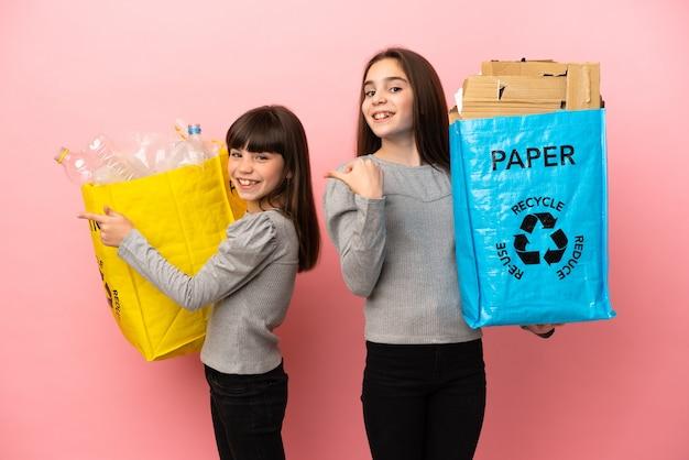 Kleine schwestern, die papier und plastik recyceln, isoliert auf rosa hintergrund, der mit dem finger zur seite in seitlicher position zeigt