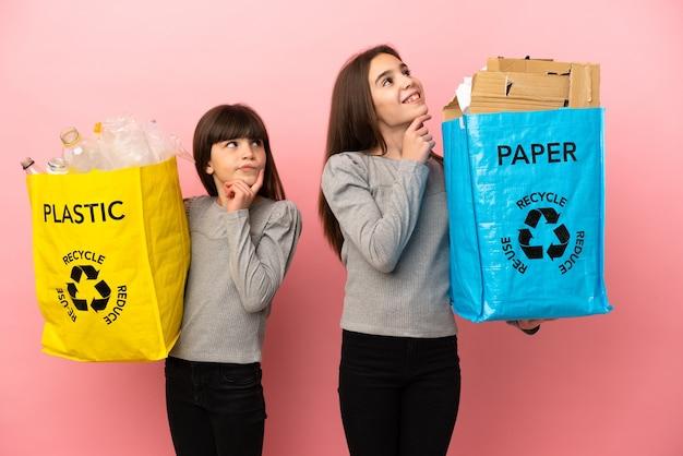 Kleine schwestern, die papier und plastik recyceln, isoliert auf rosa hintergrund und denken beim nachschlagen eine idee