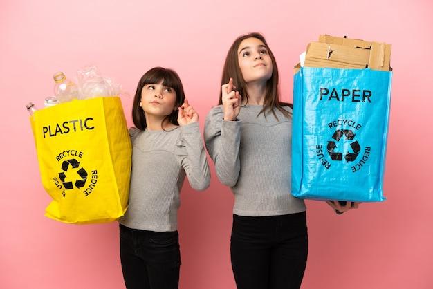 Kleine schwestern, die papier und plastik recyceln, isoliert auf rosafarbenem hintergrund mit gekreuzten fingern und wünschen das beste