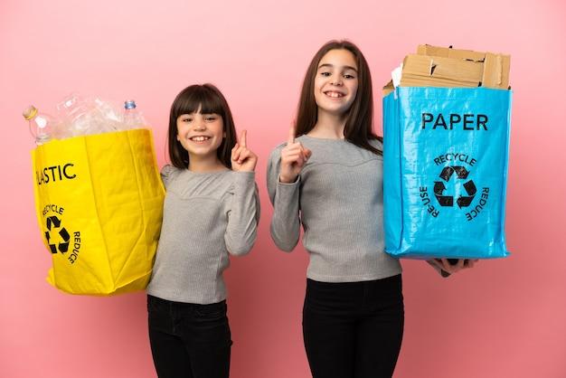 Kleine schwestern, die papier und plastik recyceln, isoliert auf rosafarbenem hintergrund und zeigen und heben einen finger im zeichen des besten
